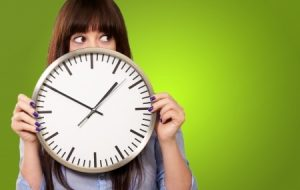 Wide-eyed girl with clock